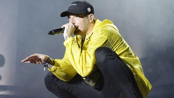 Ein Mann hockt auf einer Bühne und singt.