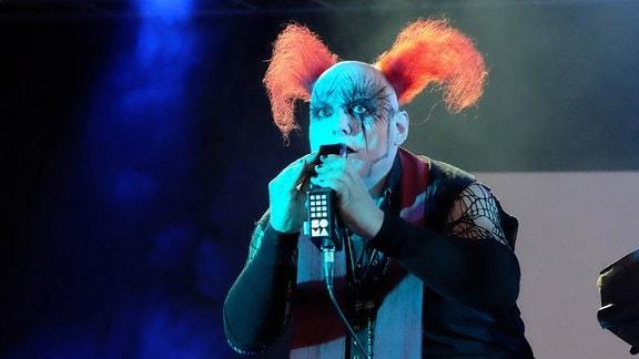 Ein kostümierter Bruno Kramm mit orangefarbenen Clowns-Haaren auf einer Bühne.