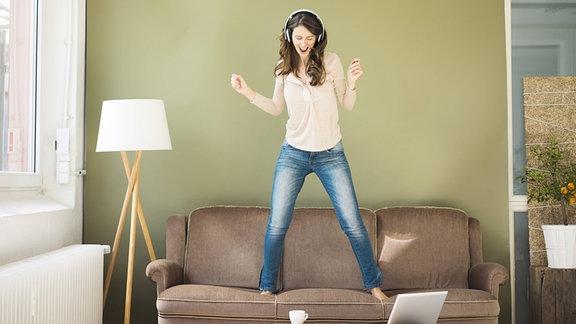 Eine junge Frau mit Kopfhörern tanzt auf einem Sofa