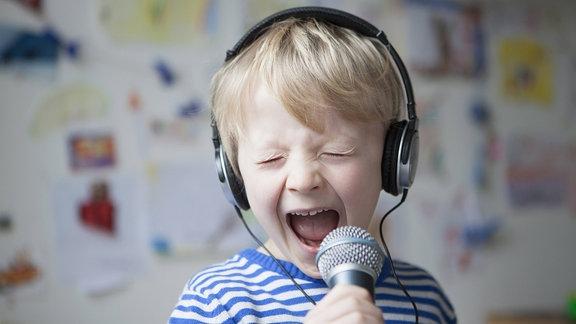 Porträt eines singenden kleinen Jungen mit Kopfhörern und Mikrophon