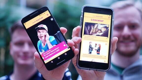 Zwei Redakteure halten Smartphones mit geöffneter MDR-Kultur-App in die Kamera.