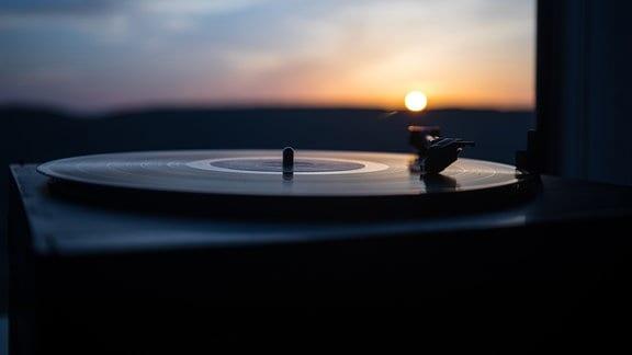Plattenspieler vor Sonnenuntergang über Bergen