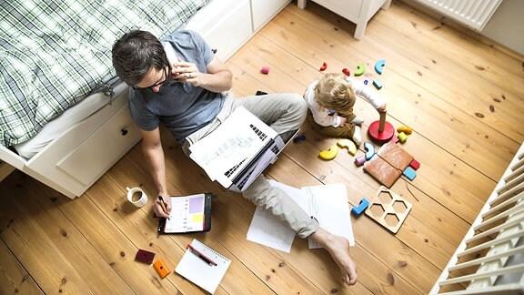 Ein Mann telefoniert an ein Kinderbett gelehnt, während neben ihm ein Kind spielt