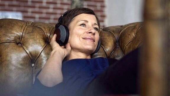 Musik hören - Frau mit Kopfhörer auf dem Sofa
