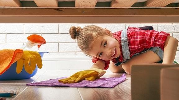 Ein Kind wischt Staub unter dem Bett.