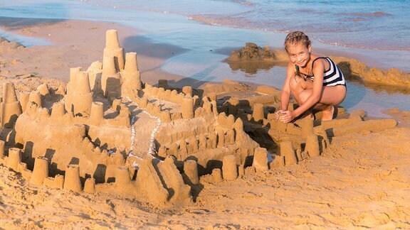 Ein Mädchen baut an einer Sandburg.