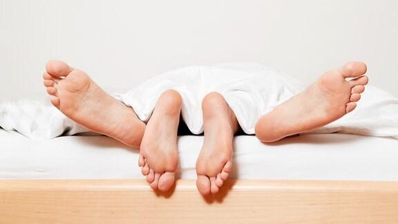 Zwei Paar Füße hängen aus einem Bett.