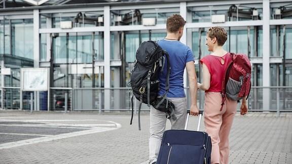 Ein Paar geht mit Koffer und Rucksäcken auf ein Parkhaus zu.