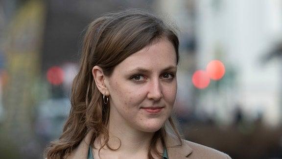 Die Autorin und freie Journalistin Valerie Schönian steht in Berlin an einer Straߟe.