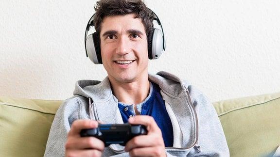 Glücklicher junger Mann spielt Videospiel auf einer Konsole