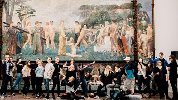 Die Auszubildenden des MDR stehen unter einem riesigen Gemälde im Leipziger Museum der bildenden Künst und stellen die Szenerie des Gemäldes nach.