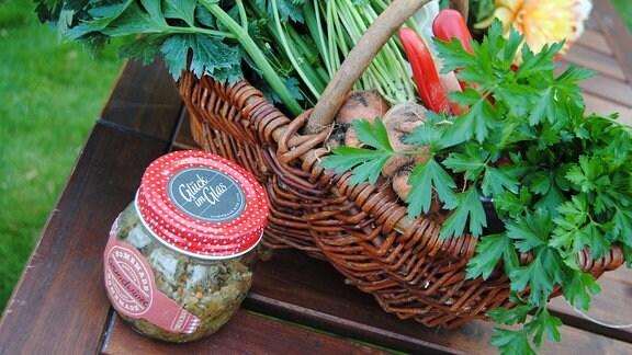 Glas mit zerkleinertem Gemüse und Salz neben einem Korb mit Gemüse und Petersilie auf einem Holztisch