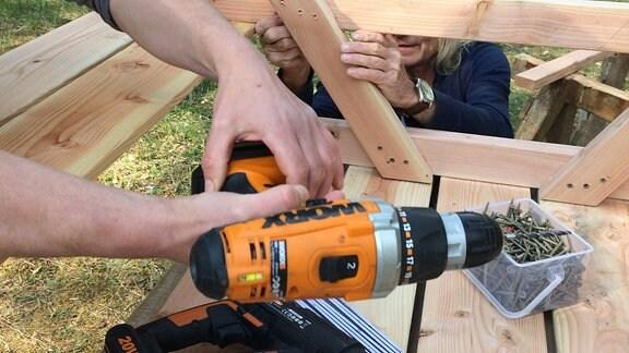 Hände halten einen Akkuschrauber. Dahinter ist eine Holzkonstruktion und ein Mann zu sehen.