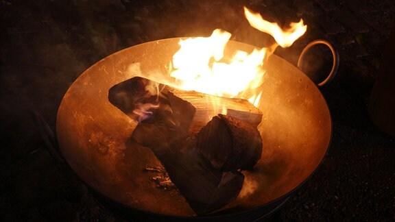 In einer Feuerschale brennen Holzscheite