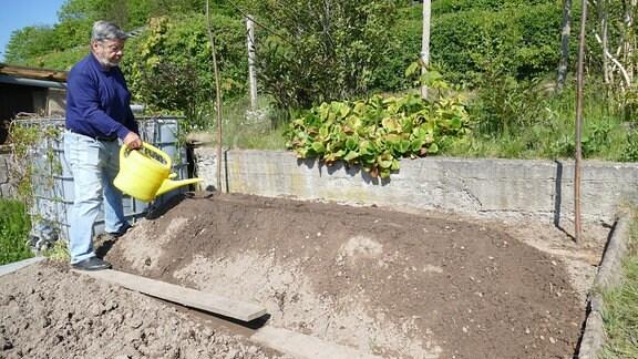 Gartenexperte Klaus Eckardt gießt Hügelbeet