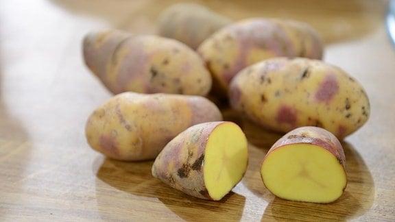 Auf einem Tisch liegt die Kartoffelsorte Mayan Twilight. Das besondere ist die gelb-violette Farbe der Schale.