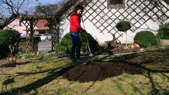 Gartenfachberaterin Brigitte Goss verteilt Kompost auf Rasenfläche