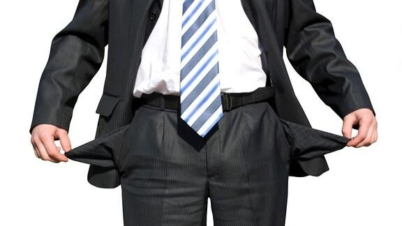 Ein Mann im Anzug zieht seine Hosentaschen nach außen.