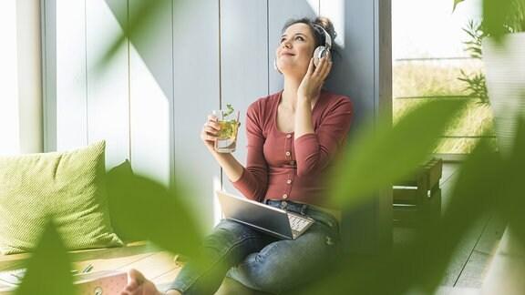 Eine weiße Frau hört mit Kopfhörern Musik, in der Hand ein gesundes Getränk, im Vordergrund unscharfe grüne Blätter