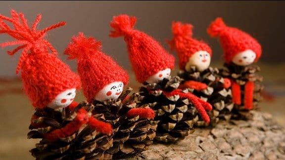 Weihnachtsmänner aus Tannenzapfen stehen in einer Reihe