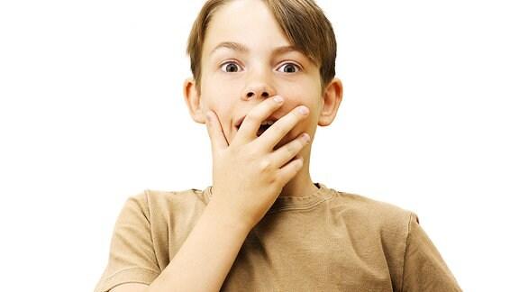 Symbolbild: Ein Junge hält sich eine Hand vor dem Mund.