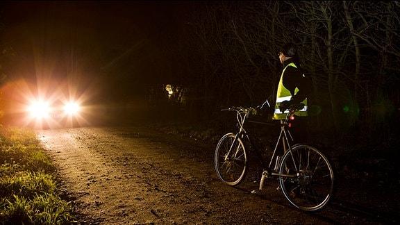 Ein Radfahrer mit Warnweste begegnet in der Dunkelheit einem Pkw