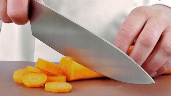 Ein Koch schneidet eine Möhre in Scheiben.