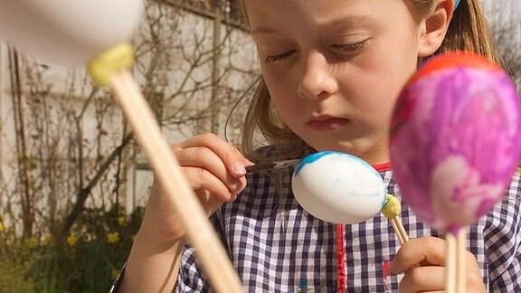 Ein Mädchen bemalt Ostereier.