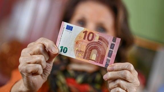 Eine Seniorin hält einen 10-Euro-Schein in der Hand