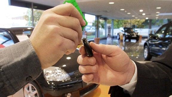 Ein Autoschlüssel wird von einer Hand in eine andere übergeben