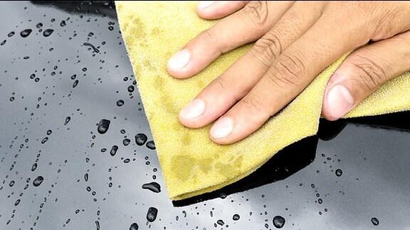 Mit einem Tuch wird ein Auto poliert.