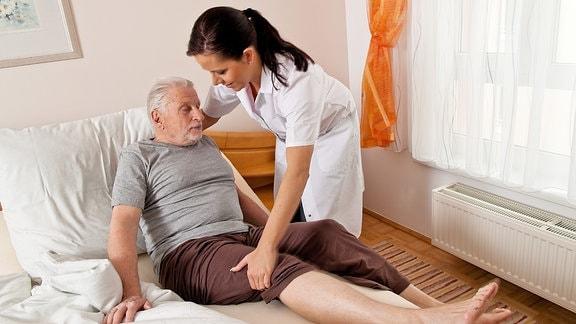 Eine Pflegerin betreut einen älteren Mann.