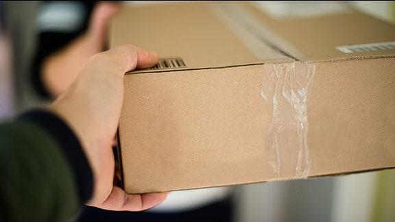 Ene Person überreicht ein Paket