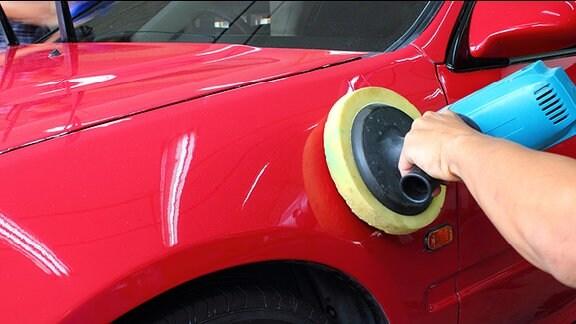 Ein rotes Auto wird mit einer Poliermaschine aufpoliert.