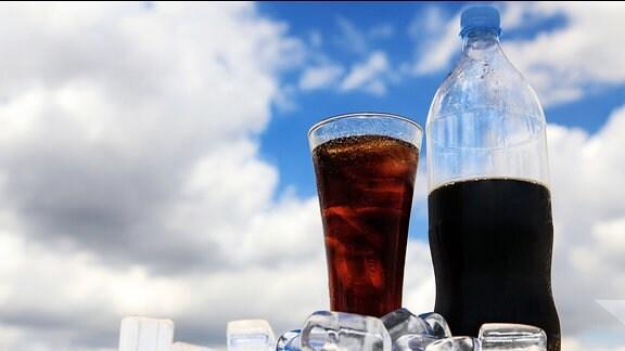 Eine Flasche und ein Glas Cola, davor liegen Eiswürfel