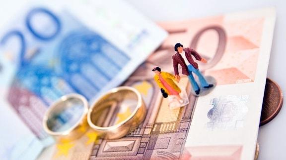 Ein Figurenpaar und zwei Ringe liegen auf Geldscheinen.