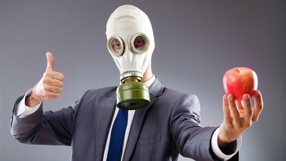 Ein Mann mit einer Gasmaske hält einen Apfel.