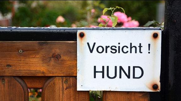 """Warnhinweis an einem Zaun """"Vorsicht! Hund""""."""