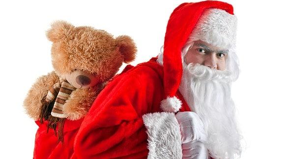 Ein Weihnachtsmann mit einem Teddy auf dem Rücken.