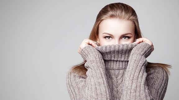 Blonde junge Frau trägt modischen Strick-Pullover vor grauem Hintergrund.