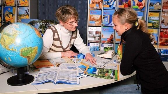 Zwei Frauen unterhalten sich im Reisebüro.