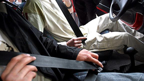 Zwei Personen schnallen sich in einem Auto an