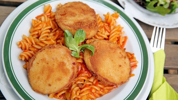 Drei panierte Scheiben Jagdwurst liegen als Jägerschnitzel auf einer Portion Spirelli mit Tomatensoße.