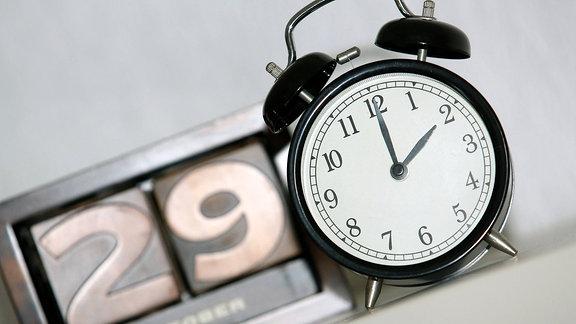 Zeitumstellung: ein Wecker zeigt zwei Uhr, im Hintergrund zeigt ein Kalender das Datum 29. Oktober.