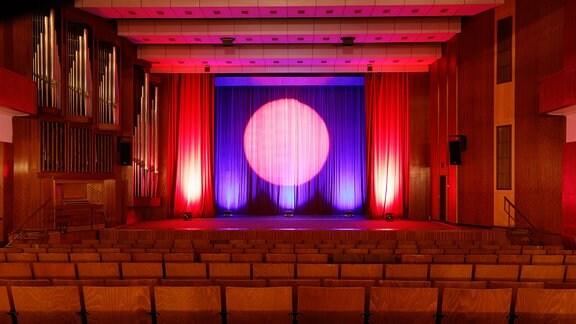 Der Saal im Kulturhaus in Gotha: Blick über leere Stuhlreihen zur Bühne, auf dem geschlossenen Vorhang ist der Kreis eines Scheinwerfers zu sehen.