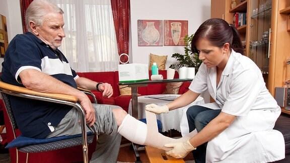 Eine Krankenschwester verbindet einem älteren Herren das Bein.