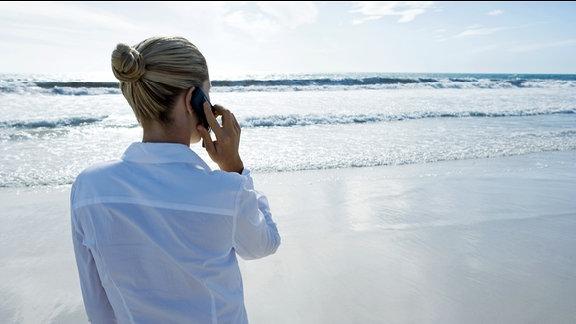 Eine Frau telefoniert im Urlaub mit ihrem Handy