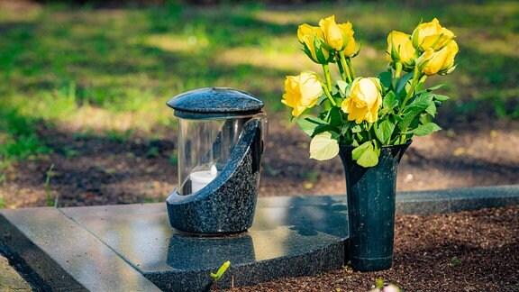 Eine Kerze und Blumen stehen auf einem Grab.