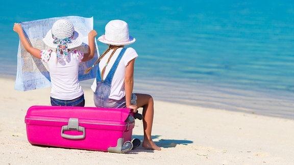 zwei Mädchen sitzen auf einem pinken Koffer und betrachten eine Landkarte