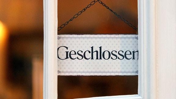 """""""Geschlossen"""" steht auf einem Schild an einer Tür eines Geschäftes"""